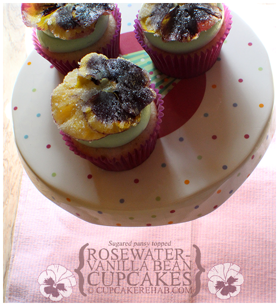 Rosewater-vanilla bean cupcakes, topped with a green-colored vanilla buttercream & sugared pansies!