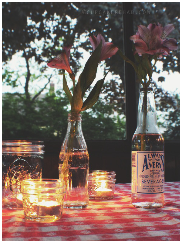 Old bottles filled with flowers on the porch table, mixed with Ball jars & candles. Classic.